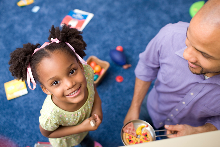 A little girl in a playroom smiles up at the camera while parent smiles down at her