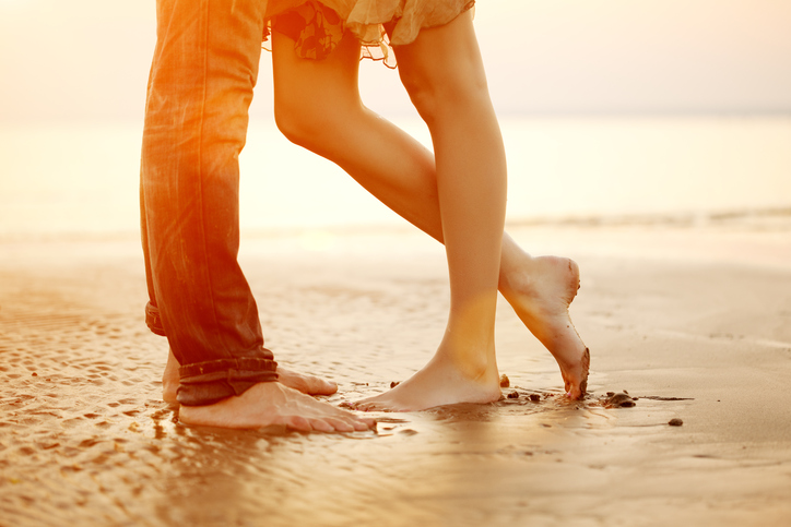 Photo showing legs of couple standing very close on shore facing each other