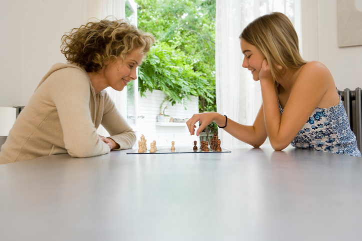 Mother plays chess with teenager at table