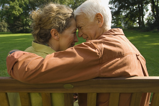 Older couple on bench smiling with heads together
