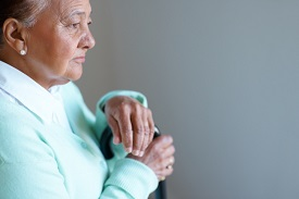 A pensive, elderly woman gazes down
