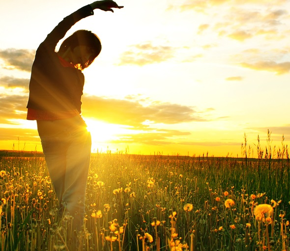 Person stretches at sunset in field of flowers