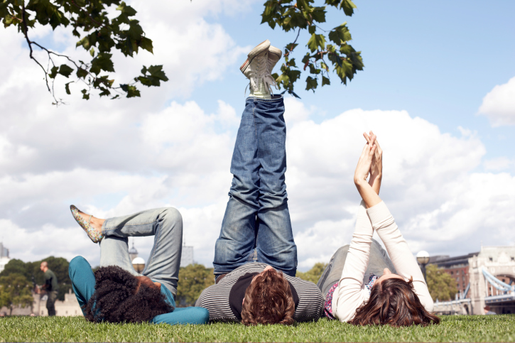 Three friends lying under a tree, legs in the air