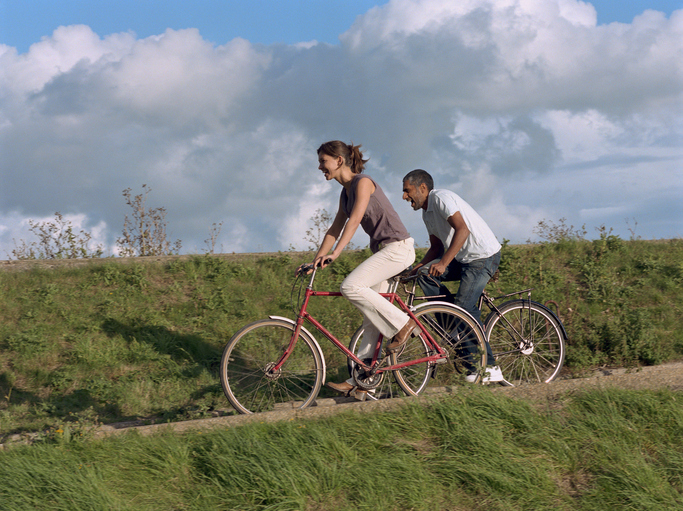 Two people bicycling down grassy hill under partly cloudy blue sky