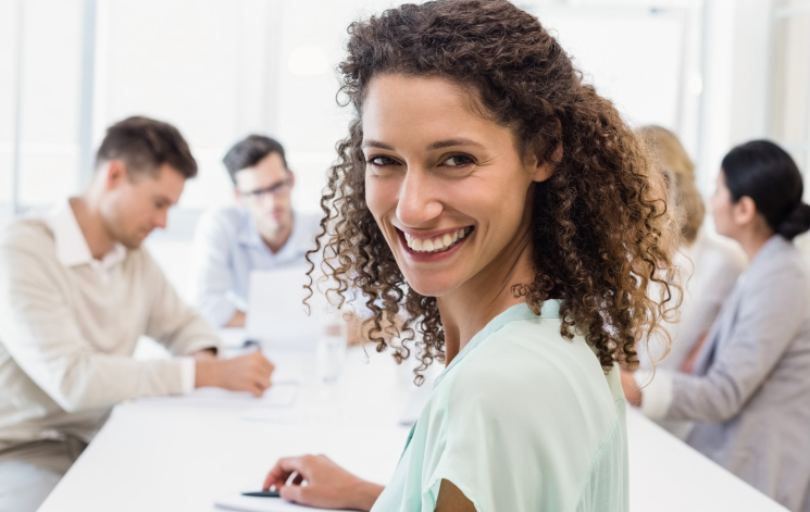 Woman in meeting smiling at camera