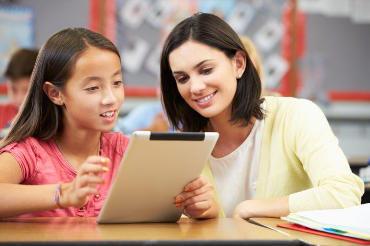 A young girl using a tablet and working with a tutor