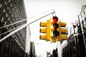Angled-up view of bright traffic light on grayscale street