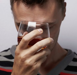 Stressed man presses glass of liquor to his forehead