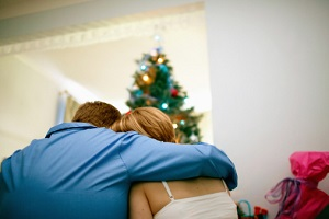 A couple embraces beneath a Christmas tree.