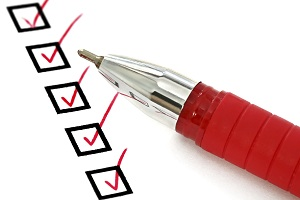 A red pen sits on a paper with five checked boxes.