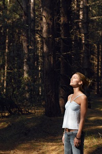 A young woman in woods looks up.
