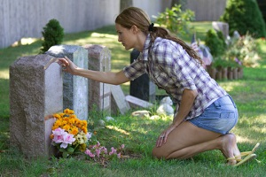 woman-kneeled-over-headstone
