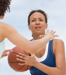 A woman looks for an opportunity to pass a basketball.