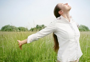 A woman stands in a grassy field and streatches her arms out while taking a deep breath.