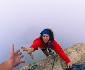 A woman reaches for a helping-hand as she climbs a rock.