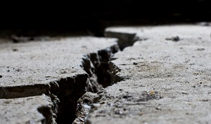 A close-up picture of a large crack in concrete pavement.