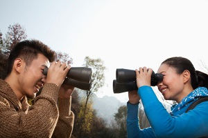 Young Asian couple in a forest smiling and  looking at each other through binoculars