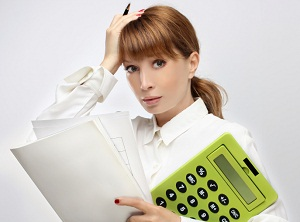 Stressed business woman holding oversized report and calculator