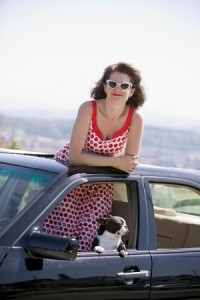 Woman in polkadot sun dress stands looking out of car's sun roof