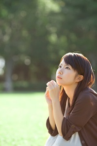 A young woman looks like she is thinking, while sitting outside.