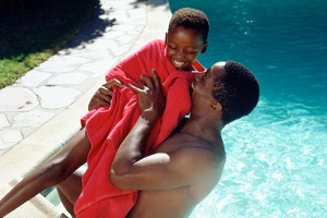 African-American father and son next to a pool in the sunshine. The father is lifting his son, who is wrapped in a red towel, up into the air in celebration. Both are smiling happily.