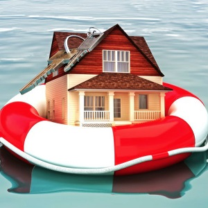 A miniature house floats in a life-preserver.