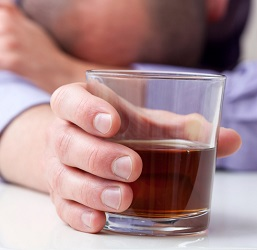 A man clasping a glass of liquor rests his head on his arm