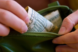 A close-up of a person's hands taking cash out of a purse.
