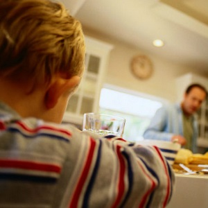 A boy sits at a kitchen table, looking sad, as his father scowls at him.
