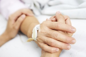 Two people holding hands in hospital