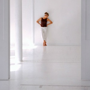 A woman stands in a stark room alolne.