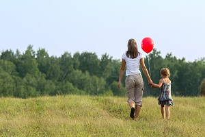 Mother and daughter walking in field with red balloon