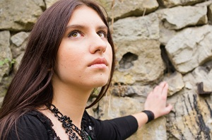 Young woman looks towards sky while leaning on stone wall