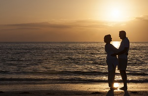 A couple faces one another on a beach at sunset.