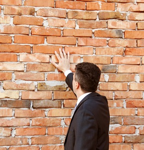 Man in a suit touching a brick wall