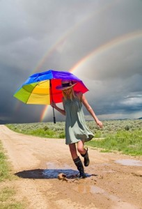 Woman skips with rainbow umbrella while strom crosses the sky