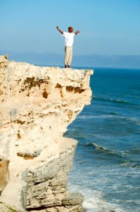 Man with arms raised standing on seaside cliff