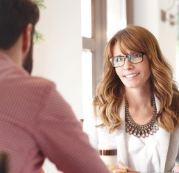 Woman looks attentively at man in during consultation