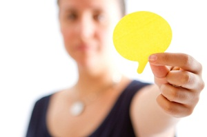Woman holding cut out speech bubble