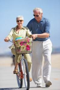 An older man helps his wife ride a bike