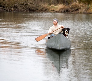 Young man and his dog canoeing