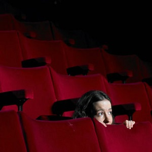 A young woman crouches down and peers over a seat in an empty theater.