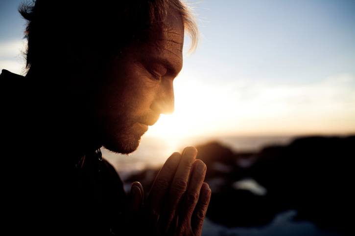 A man prays at sunset