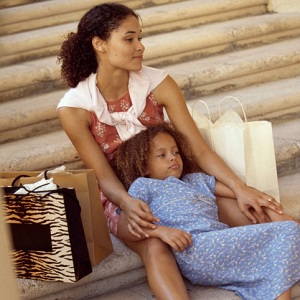 A mother sits on outside steps as her daughter sits, slouching down, in front of her.