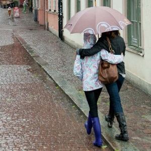 Two women walk with their arms around each other while sharing an umbrella.