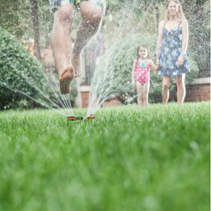 A father jumps over a sprinkler as his wife and daughter watch.