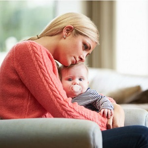 A woman looks depressed as she holds her baby.