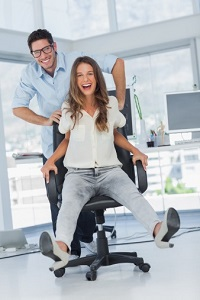 A man wheels a female co-worker around in an office chair