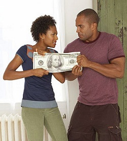 Couple fighting over oversized money