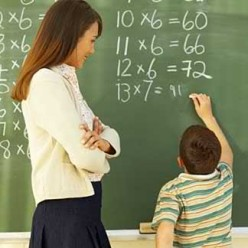 Child doing multiplication on chalkboard